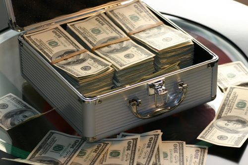 a metal case of 100 dollar bills showing the cost of exclusive beats