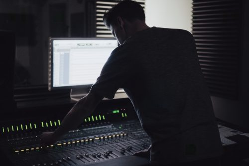 man in studio making a beat that is available for exclusive rights