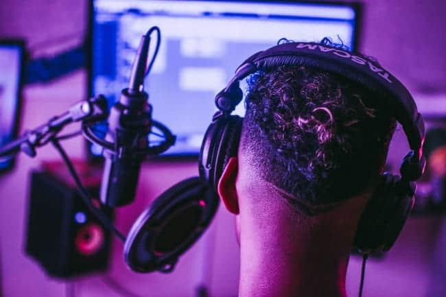 man in music studio with headphones on listening to exclusive beats